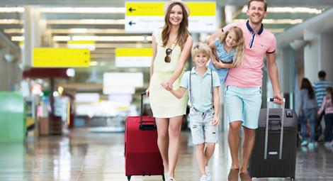 family walking through an airport terminal